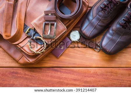 Men's casual outfits with leather accessories on wooden background