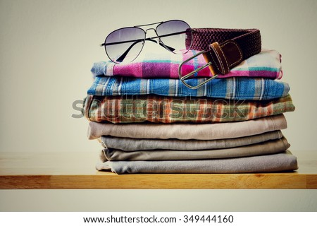 Men's casual outfits with pants, plaid shirt, brown belt and sunglasses on wooden table over gray wall grunge background - stock photo
