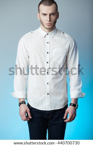Men's clothing concept. Portrait of fashionable young man with haircut wearing trendy clothes & posing over blue and gray background. Casual street style. Studio shot