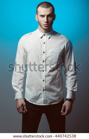 Men's clothing concept. Portrait of fashionable young man with haircut wearing trendy clothes & posing over blue and gray background. Casual street style. Studio shot - stock photo