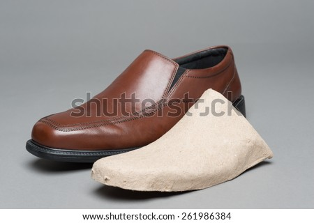 Men's dress shoes are sometimes packaged with cardboard inserts that prevent the shoe from getting deformed.  - stock photo