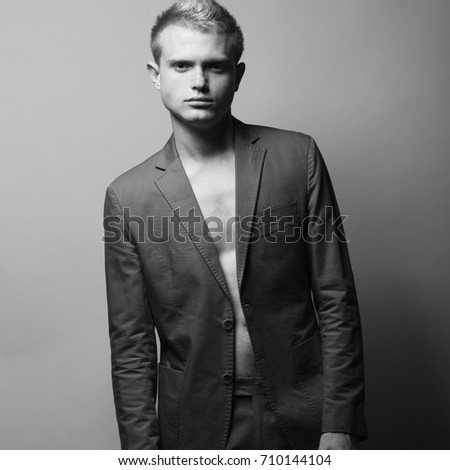 Men's fashion concept. Portrait of gorgeous blond fashion model in gray jacket posing over gray background. Monochrome studio shot