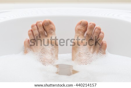 Men's feet in a bright white bathtub, selective focus on toes