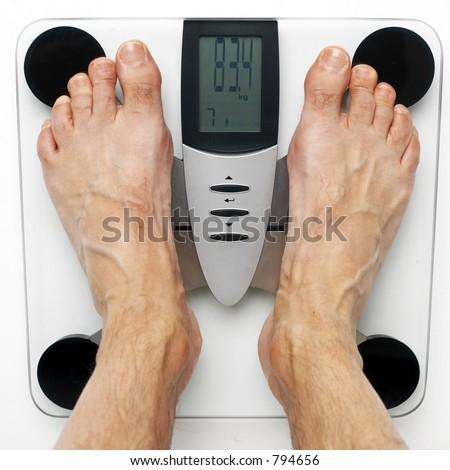 men's feet on an electronic, design balance scale - stock photo