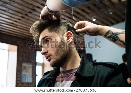Men's haircut at the barber scissors - stock photo
