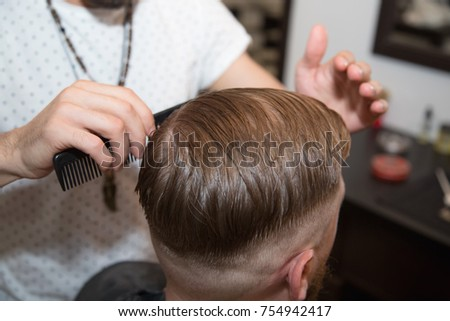 Men's hairstyling and haircutting with hair clipper in a barber shop or hair salon. Bearded brutal man in a barber shop.