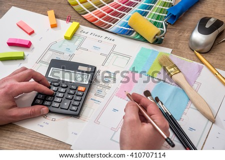 Men's hand drawing home with color sample, work tools, calculator - stock photo