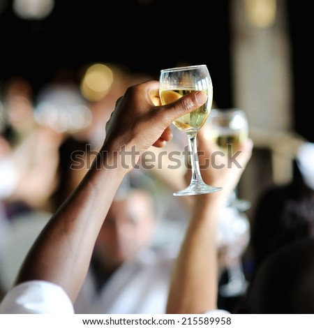 Men's hand holding wine glass at festive event - stock photo