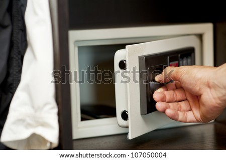 Men's hand opens a safe hidden in the wardrobe. Small home or hotel safe - stock photo