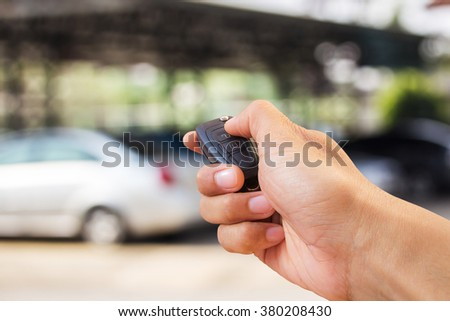Men's hand presses on the remote control car alarm systems