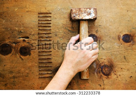 Men's hand takes a hammer which is on old wooden table with nails. Rustic vintage style. Top view. Retro concept background. - stock photo