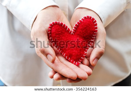 Men's hands hold a toy heart. toning. selective Focus