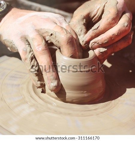 Men's hands. Potter at work. Creating dishes. Potter's wheel. Dirty hands in the clay and the potter's wheel with the product. Creation. Potter work. At high speeds. Creativity, working with hands. - stock photo
