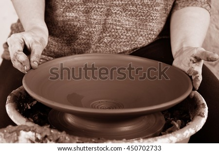 Men's hands. Potter at work. Creating dishes. Potter's wheel. Dirty hands in the clay and the potter's wheel with the product. Creation. Working potter.