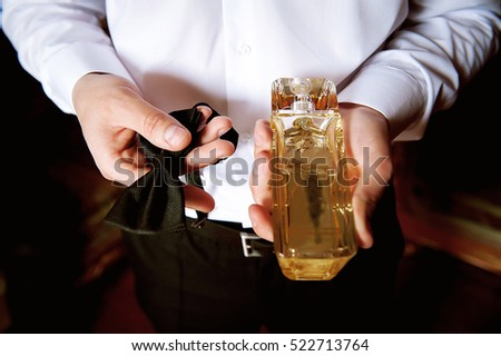 men's hands with a tie and toilet water