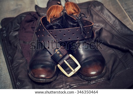 Men's leather jacket, high boots and a leather belt with buckle - stock photo
