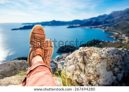Men's legs in the brown shoes lying on the mountain on the sea scape background - stock photo