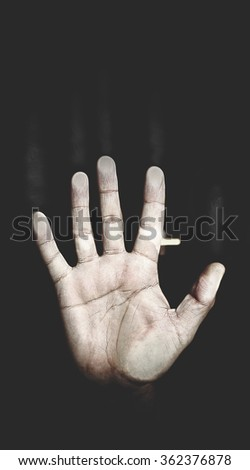 Men's palm pressed to the glass on the black background, the metaphor of despair
