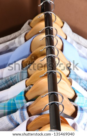 Men's shirts on hangers on brown background - stock photo