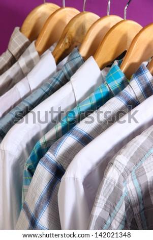 Men's shirts on hangers on purple background - stock photo