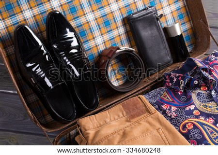 Men's shoes, accessories and clothes in old suitcase. Still life of menswear. - stock photo