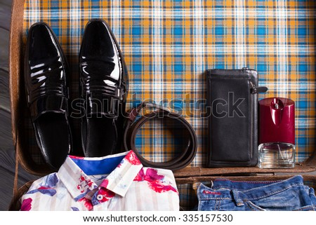 Men's shoes and accessories in the open suitcase. Men's things of gentleman. - stock photo