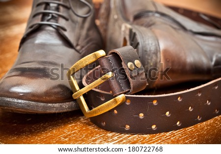 men's shoes and leather belt brown with gold buckle. cowboy style - stock photo