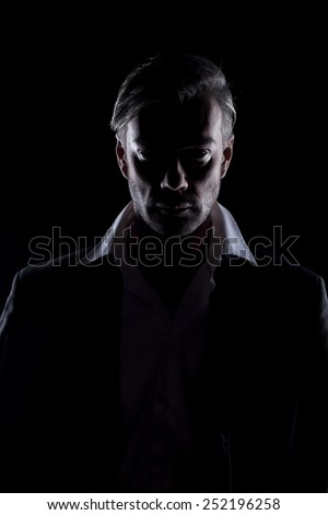 Men's silhouette in the dark looking at you - stock photo