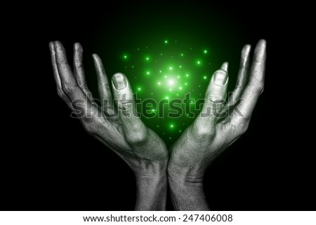 Men's silver hand with magical energy on a black background - stock photo