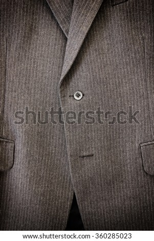 Men's two-button grey woolen suit - the way for correct buttoning.