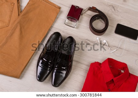 Men's wardrobe. Men's set of clothes and accessories on a wooden background. - stock photo