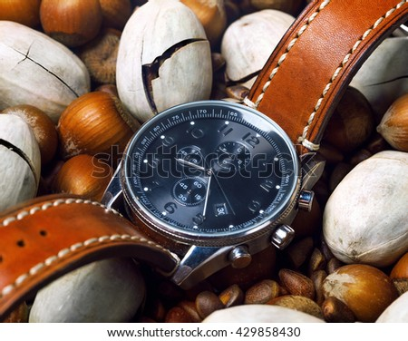 men's watch close up lying flat on the nuts - stock photo