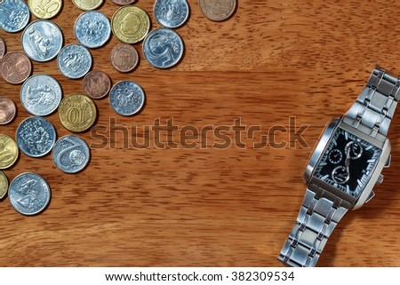 Men's wrist watch and metal coins as in time is money concept - stock photo