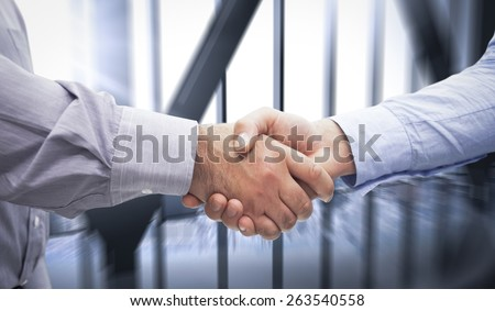 Men shaking hands against room with large window looking on city