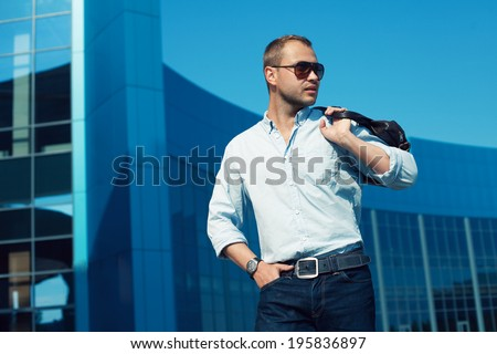 Men Shopping concept. Portrait of attractive smiling man in trendy casual clothing with leather bag and sunglasses posing over shopping mall. Sunny spring weather with blue sky. Outdoor shot