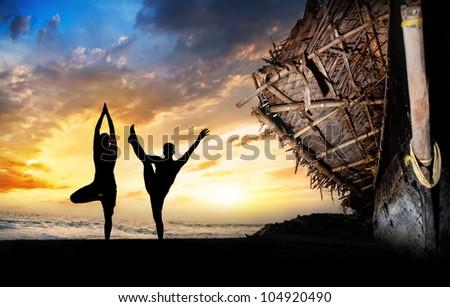 Men silhouettes doing utthita Hasta Padangustasana and vrikshasana poses on the beach near the fisherman boat at sunset background in India - stock photo