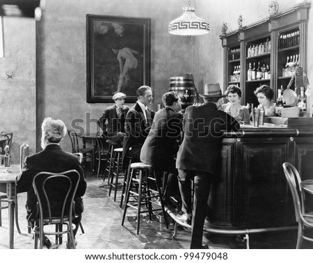 Men sitting around a counter in a bar - stock photo