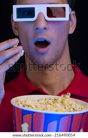 Men sitting at cinema and eating popcorn. Excited young men in glasses watching movie - stock photo