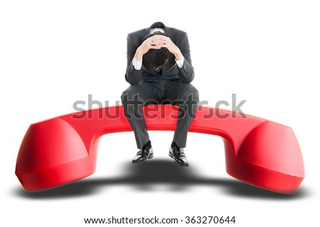 Men sitting on top of the red handset, trouble - stock photo