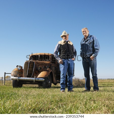 Men Standing Beside an Old Automobile - stock photo