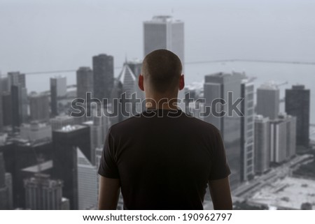 Men standing on the rooftop of a skyscraper over a cityscape