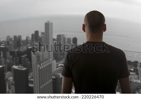 Men standing on the rooftop of a skyscraper over a cityscape - stock photo