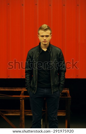Men street fashion concept. Portrait of brutal young man with short hair wearing black jacket, jeans and posing over red urban background. Hands in pockets. Hipster style. Outdoor shot - stock photo