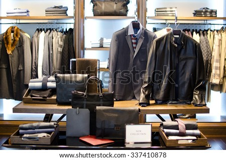 Men suits ans shoes hanging in a luxury clothing store. - stock photo