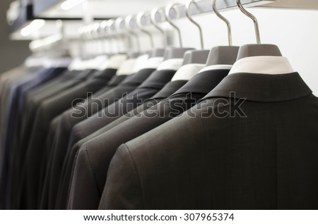 Men suits hanging in a clothing store. - stock photo