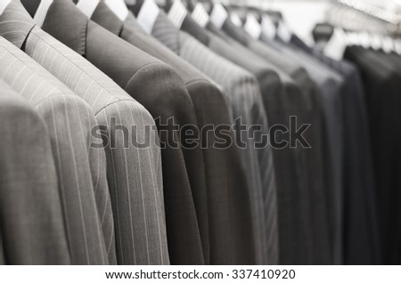 Men suits hanging in a clothing store.