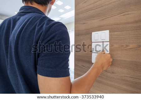 men switching off the light ,saving concept - stock photo