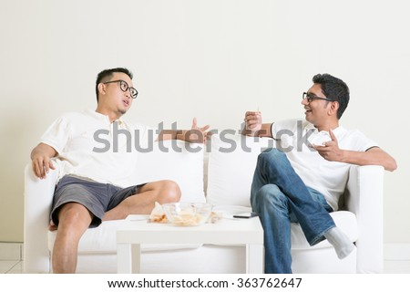 Men talk concept. Two young male friend sitting on sofa and chatting at home. Multiracial people friendship.