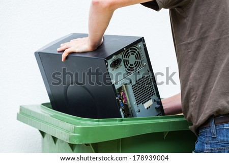 Men throwaway hardware into container - stock photo