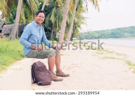 Men traveler with backpack using mobile phone at the beach